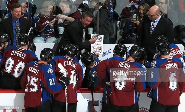 Head coach Patrick Roy of the Colorado Avalanche draws up a play during a time out as assistant coaches Tim Army and Andre Tourigny look on against...