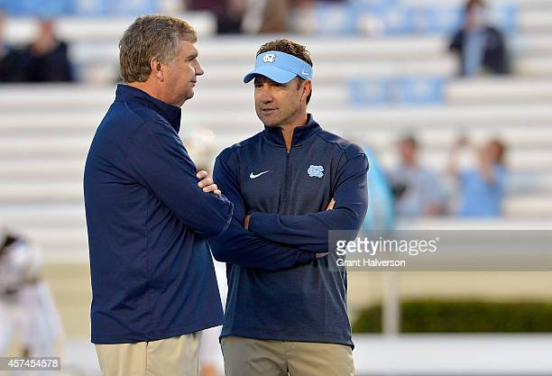 Head coach Paul Johnson of the Georgia Tech Yellow Jackets left talks with head coach Larry Fedora of the North Carolina Tar Heels before their game...