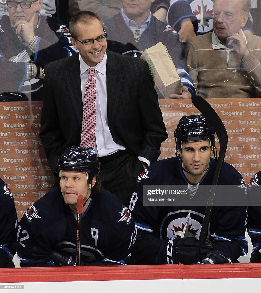 Head coach <a gi-track='captionPersonalityLinkClicked' href=/galleries/search?phrase=Paul+Maurice+-+Coach&family=editorial&specificpeople=13636283 ng-click='$event.stopPropagation()'>Paul Maurice</a> of the Winnipeg Jets smiles as he stands behind Olli Jokinen #12 and Patrice Cormier #28 on the bench in third-period action in an NHL game against the Boston Bruins at the MTS Centre on April 10, 2014 in Winnipeg, Manitoba, Canada.