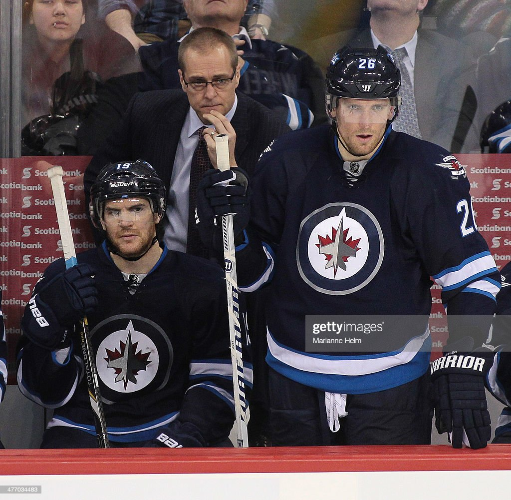 Head coach Paul Maurice of the Winnipeg Jets watches the action from the bench as he stands behind Jim Slater #19 and <a gi-track='captionPersonalityLinkClicked' href=/galleries/search?phrase=Blake+Wheeler&family=editorial&specificpeople=716703 ng-click='$event.stopPropagation()'>Blake Wheeler</a> #26 in third-period action in an NHL game against the Los Angeles Kings at the MTS Centre on March 6, 2014 in Winnipeg, Manitoba, Canada.