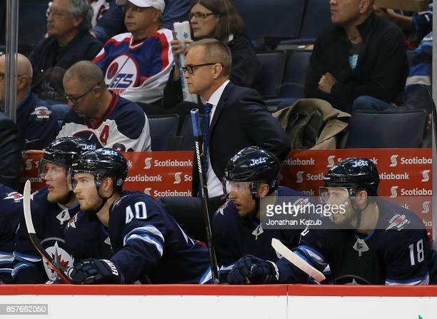 Head Coach Paul Maurice Patrik Laine Joel Armia Blake Wheeler and Bryan Little of the Winnipeg Jets keep an eye on the play from the bench during...
