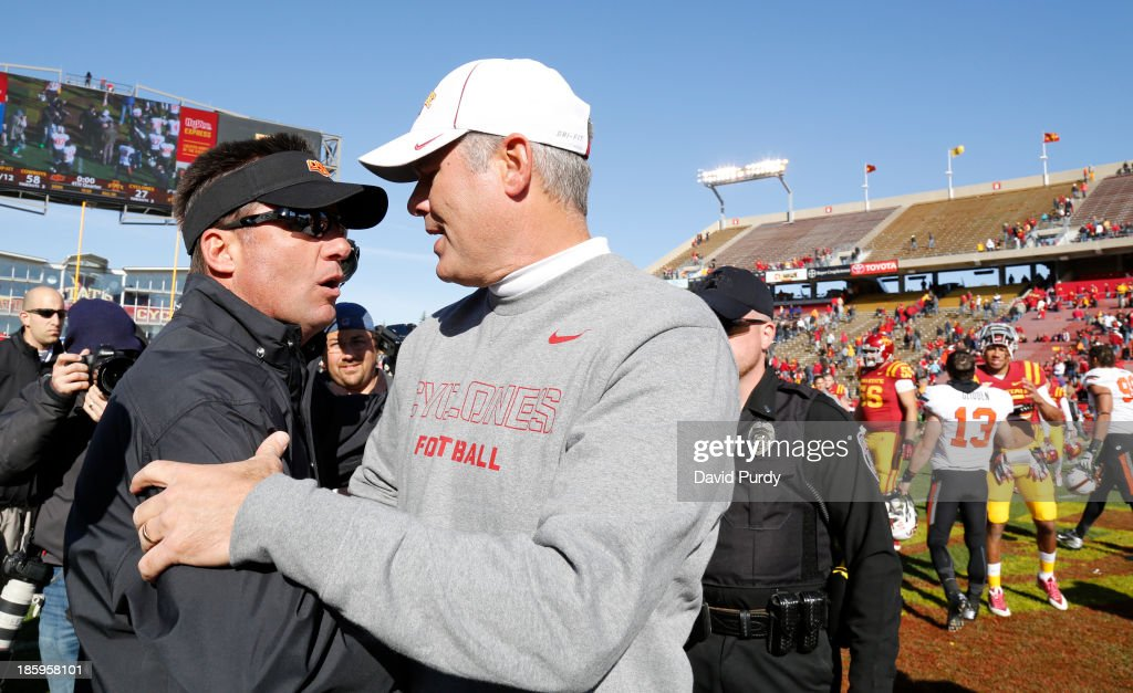 Head coach Paul Rhoads of the Iowa State Cyclones rushes shakes hands with head coach Mike Gundy of the Oklahoma State Cowboys after the Cowboys defeated the Cyclones 58-27 at Jack Trice Stadium on October 26, 2013 in Ames, Iowa. The Oklahoma State Cowboys defeated the Iowa State Cyclones 58-27.