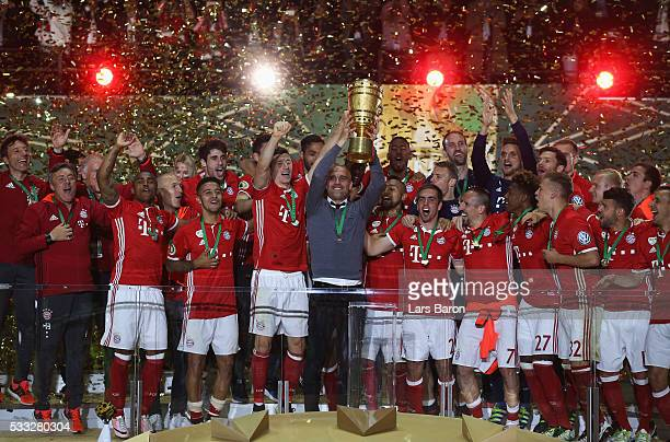 Head coach Pep Guardiola of Bayern Muenchen lifts the trophy after winning the DFB Cup final match in a penalty shootout against Borussia Dortmund at...