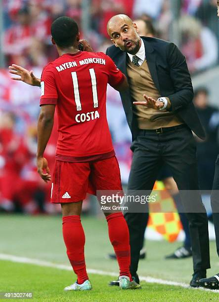 Head coach Pep Guardiola of Muenchen talks to Douglas Costa during the Bundesliga match between FC Bayern Muenchen and Borussia Dortmund at Allianz...
