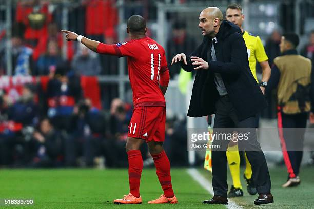Head coach Pep Guardiola of Muenchen talks to Douglas Costa during the UEFA Champions League Round of 16 Second Leg match between FC Bayern Muenchen...