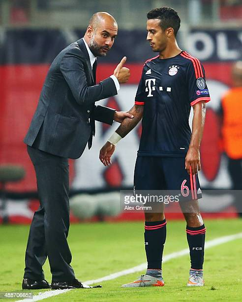 Head coach Pep Guardiola of Muenchen talks to Thiago Alcantara during the UEFA Champions League Group F match between Olympiacos FC and FC Bayern...