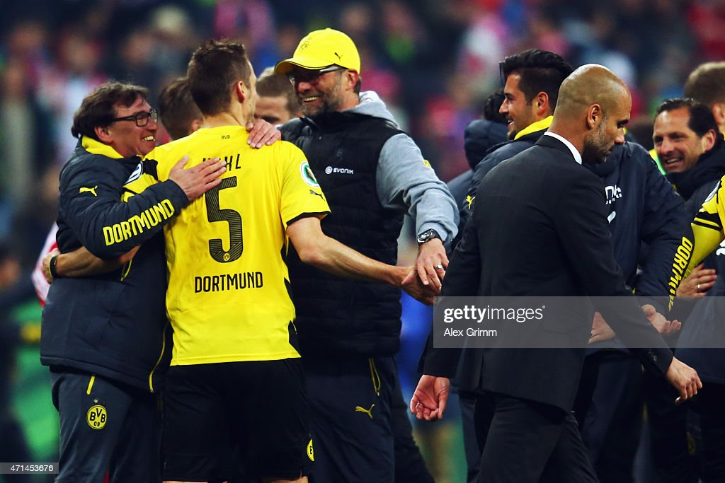 Head coach Pep Guardiola of Muenchen walks by as Juergen Klopp of Dortmund celebrates with <a gi-track='captionPersonalityLinkClicked' href=/galleries/search?phrase=Sebastian+Kehl&family=editorial&specificpeople=486611 ng-click='$event.stopPropagation()'>Sebastian Kehl</a> after the DFB Cup Semi Final match between FC Bayern Muenchen and Borussia Dortmund at Allianz Arena on April 28, 2015 in Munich, Germany.