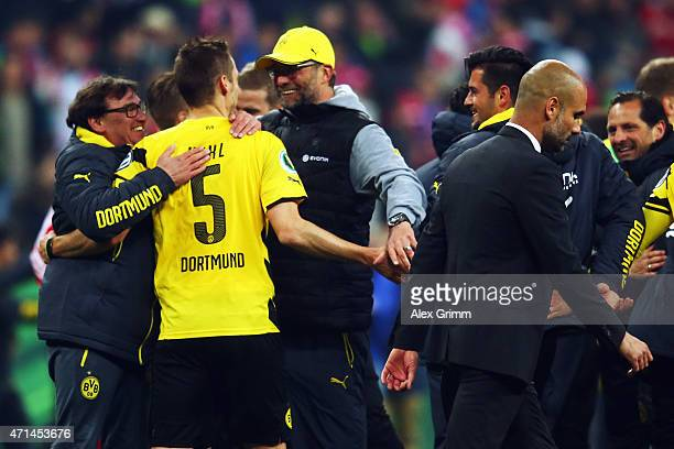 Head coach Pep Guardiola of Muenchen walks by as Juergen Klopp of Dortmund celebrates with Sebastian Kehl after the DFB Cup Semi Final match between...
