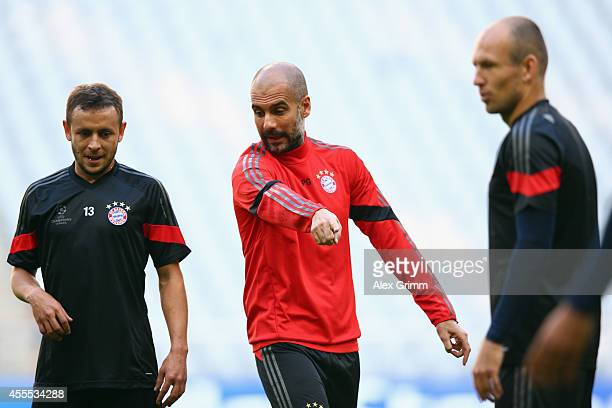 Head coach Pep Guardiola talks to Rafinha and Arjen Robben during the FC Bayern Muenchen training session ahead of their UEFA Champions League Group...