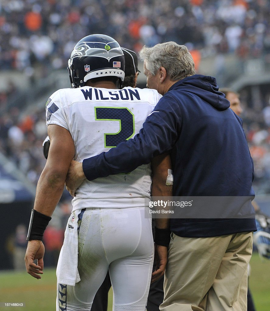 Head coach Pete Carroll of the Seattle Seahawks and Russell Wilson #3 walk off the field after a victory on December 2, 2012 at Soldier Field in Chicago, Illinois.The Seattle Seahawks defeated the Chicago Bears 23-17 in overtime.
