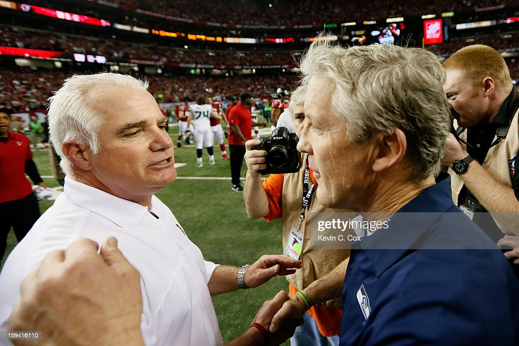 Head coach Pete Carroll of the Seattle Seahawks congratulates head coach Mike Smith of the Atlanta Falcons after the Falcons defeated the Seahawks 30 to 28 during the NFC Divisional Playoff Game at Georgia Dome on January 13, 2013 in Atlanta, Georgia.