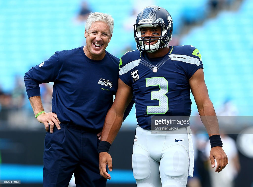 Head coach <a gi-track='captionPersonalityLinkClicked' href=/galleries/search?phrase=Pete+Carroll+-+Head+Coach&family=editorial&specificpeople=213057 ng-click='$event.stopPropagation()'>Pete Carroll</a> of the Seattle Seahawks talks with his quarterback <a gi-track='captionPersonalityLinkClicked' href=/galleries/search?phrase=Russell+Wilson+-+American+Football+Quarterback&family=editorial&specificpeople=2292912 ng-click='$event.stopPropagation()'>Russell Wilson</a> #3 of the Seattle Seahawks before their game against the Carolina Panthers at Bank of America Stadium on September 8, 2013 in Charlotte, North Carolina.