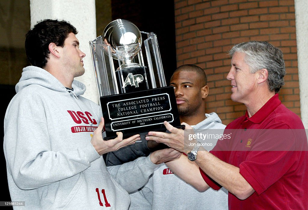 Head coach Pete Carroll of the University of Southern California hands the Associated Press 2003 College Football National Championship trophy to...
