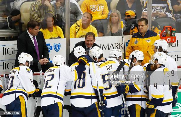 Head coach Peter Laviolette and assistant coach Phil Housley of the Nashville Predators speak to their team during the third period in Game One of...