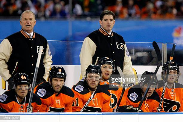 Head Coach Peter Laviolette of the Philadelphia Flyers looks on against the New York Rangers during the 2012 Bridgestone NHL Winter Classic at...