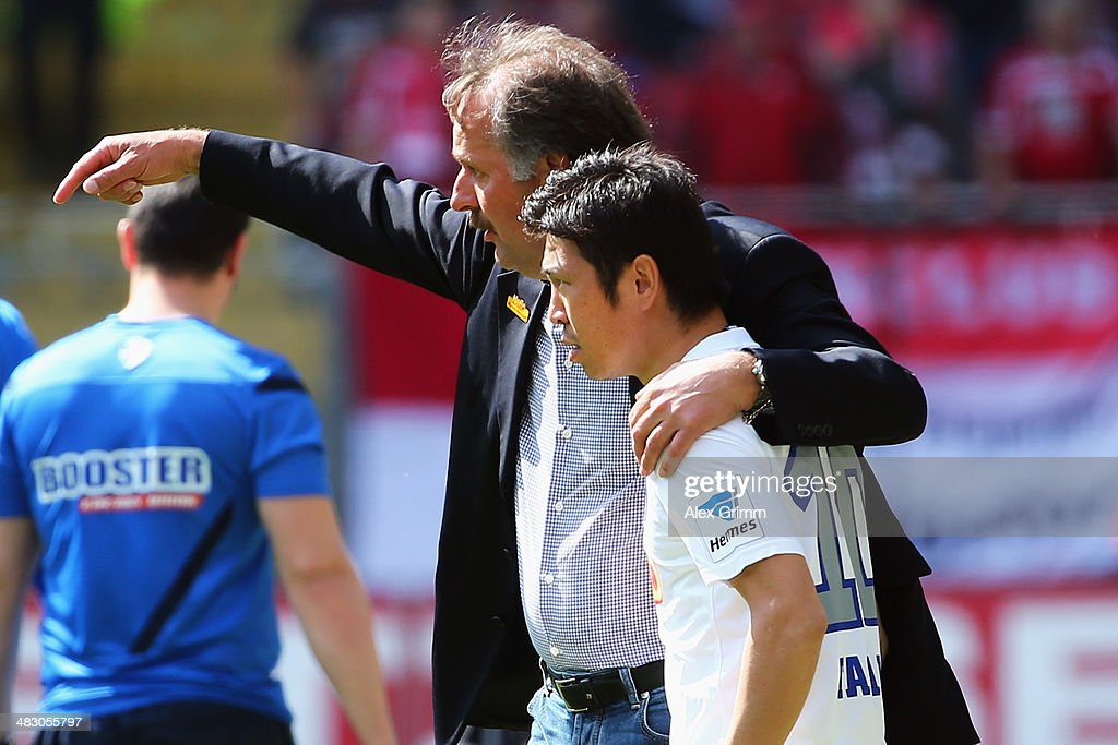 Head coach Peter Neururer of Bochum talks to Yusuke Tasaka during the Second Bundesliga match between 1 FC Kaiserslautern and VfL Bochum at...