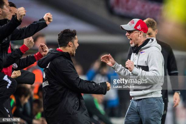 Head Coach Peter Stoeger and team mates react after winning the Bundesliga match between 1 FC Koeln and Werder Bremen at RheinEnergieStadion on May 5...