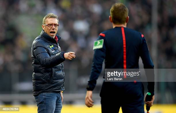 Head coach Peter Stoeger discusses with assistant referee MArkus Haecker during the Bundesliga match between Borussia Moenchengladbach and 1 FC Koeln...