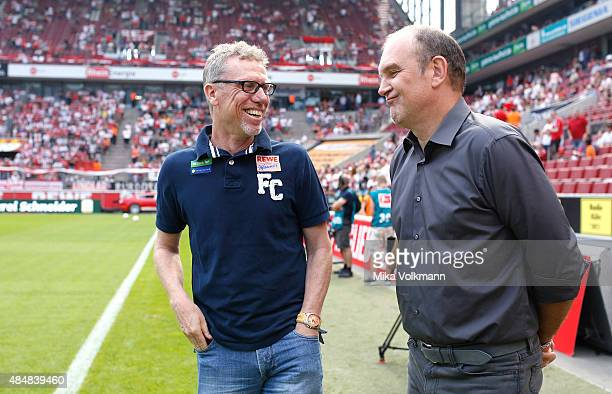 Head Coach Peter Stoeger of Cologne and Joerg Schmadtke of Cologne laugh together during the Bundesliga match between 1 FC Koeln and VfL Wolfsburg at...