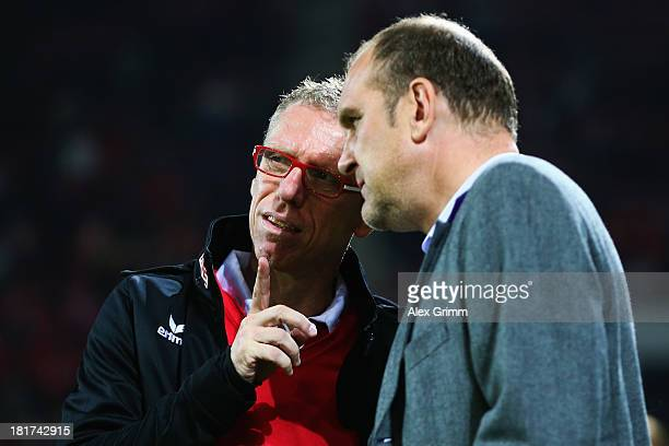 Head coach Peter Stoeger of Koeln and manager Joerg Schmadtke chat prior to the DFB Cup second round match between 1 FSV Mainz 05 and 1 FC Koeln at...
