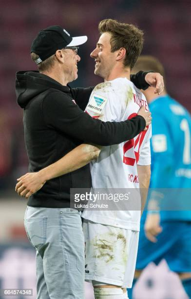 Head Coach Peter Stoeger of Koeln embraces Lukas Kluenter of Koeln after winning the Bundesliga match between 1 FC Koeln and Eintracht Frankfurt at...
