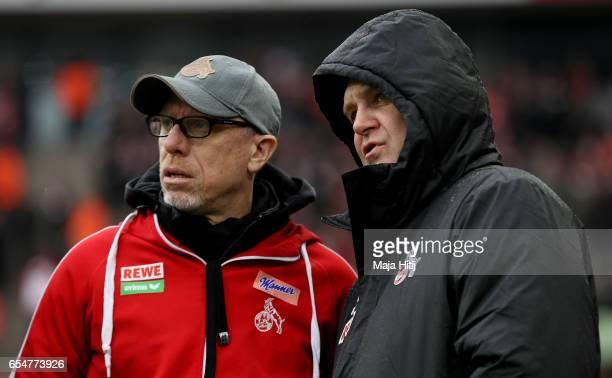 Head coach Peter Stoeger of Koeln is seen with sports director Joerg Schmadtke during the Bundesliga match between 1 FC Koeln and Hertha BSC at...