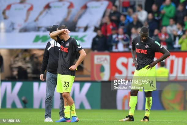 Head coach Peter Stoeger of Koeln walks to his players Matthias Lehmann and Sehrou Guirassy after the Bundesliga match between FC Augsburg and 1 FC...