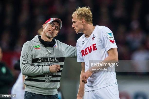 Head Coach Peter Stoeger talks to Frederik Soerensen during the Bundesliga match between 1 FC Koeln and Werder Bremen at RheinEnergieStadion on May 5...