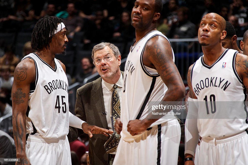 Head Coach P.J. Carlesimo of the Brooklyn Nets speaks with players Gerald Wallace #45, Andray Blatche #0 and Keith Bogans #10 during a game against the San Antonio Spurs on February 10, 2013 at the Barclays Center in the Brooklyn borough of New York City.