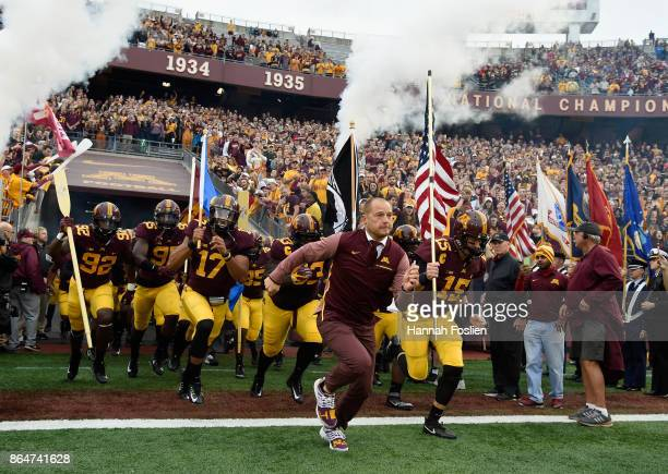 Head coach PJ Fleck of the Minnesota Golden Gophers leads his team onto the field before the game against the Illinois Fighting Illini on October 21...