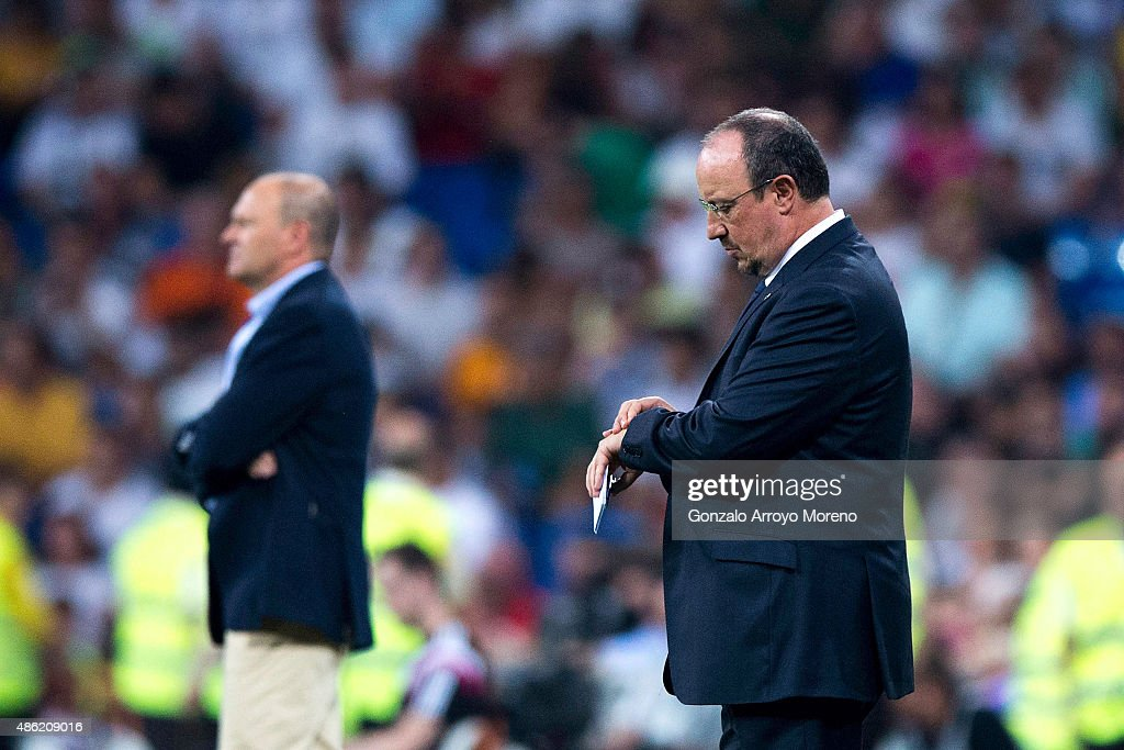 Head coach Rafael Benitez of Real Madrid CF sets his watch ahead Pepe Mel of Real Betis Balompie during the La Liga match between Real Madrid CF and Real Betis Balompie at Estadio Santiago Bernabeu on August 29, 2015 in Madrid, Spain.