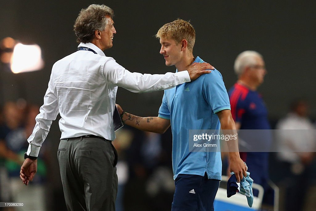 Head coach <a gi-track='captionPersonalityLinkClicked' href=/galleries/search?phrase=Rainer+Adrion&family=editorial&specificpeople=2380316 ng-click='$event.stopPropagation()'>Rainer Adrion</a> of Germany hugs <a gi-track='captionPersonalityLinkClicked' href=/galleries/search?phrase=Lewis+Holtby&family=editorial&specificpeople=5351202 ng-click='$event.stopPropagation()'>Lewis Holtby</a> after the UEFA European U21 Championship Group B match between Russia and Germany at Netanya Stadium on June 12, 2013 in Netanya, Israel.