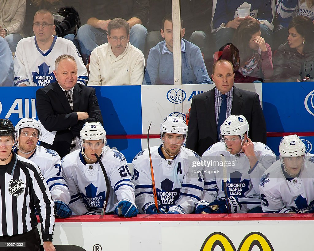 Head coach Randy Carlyle and assistant coach Steve Spott of the Toronto Maple Leafs watches the action from the bench during a NHL game against the...