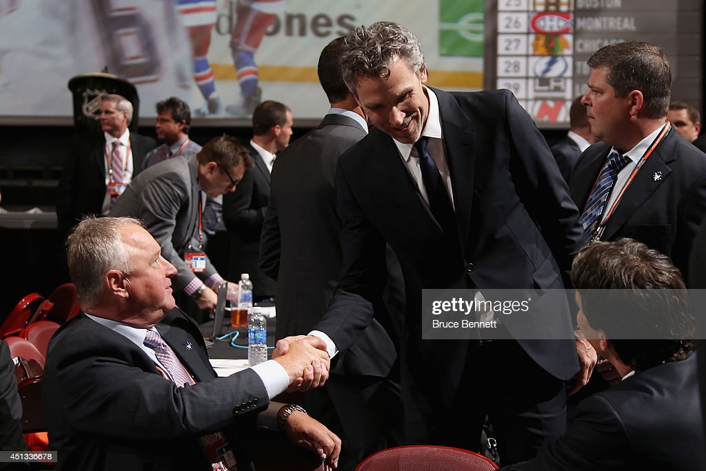 Head Coach Randy Carlyle and Brendan Shanahan President of the Toronto Maple Leafs speak to Trevor Linden President of Hockey Operations for the...