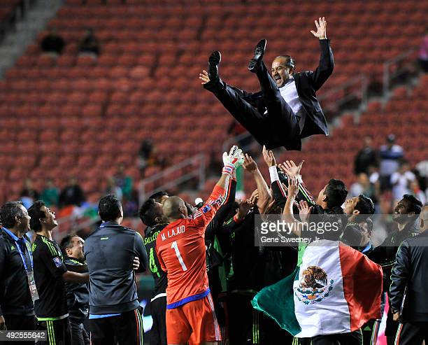 Head coach Raul Gutierrez of Mexico is thrown into the air by his team after their 20 win over Honduras to win the championship in the final CONCACAF...