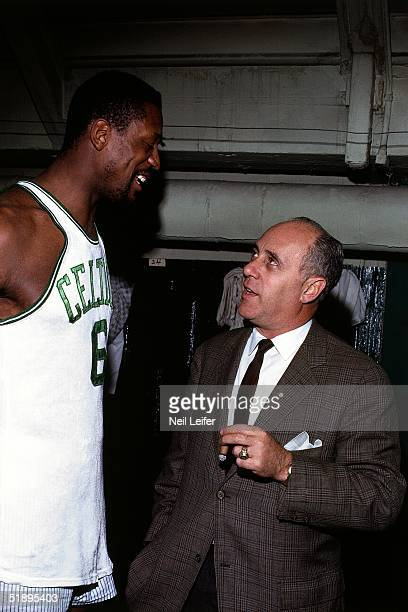 Head coach Red Auerbach of the Boston Celtics talks with Bill Russell in the locker room after playing an NBA game at the Boston Garden in Boston...