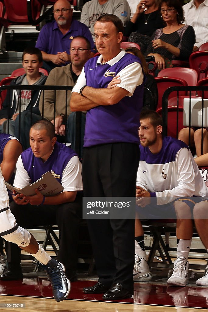 Head coach Rich Rider of the Cal Lutheran Kingsmen looks on from in front of the bench along with assistant coach Brendan Garrett (seated, L) against the Loyola Marymount Lions during the exhibition game at Gersten Pavilion on November 2, 2013 in Los Angeles, California. Loyola Marymount won 96-64.