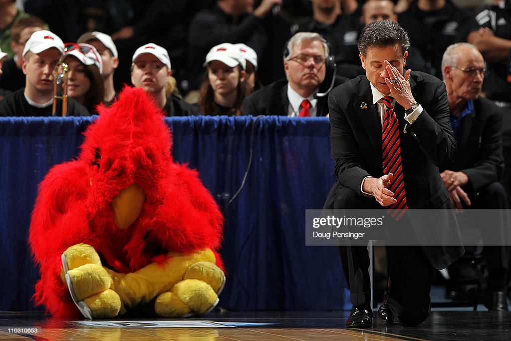 Head coach Rick Pitino of the Louisville Cardinals and the teams mascot react after a play while playing against the Morehead State Eagles during the second round of the 2011 NCAA men's basketball tournament at Pepsi Center on March 17, 2011 in Denver, Colorado.