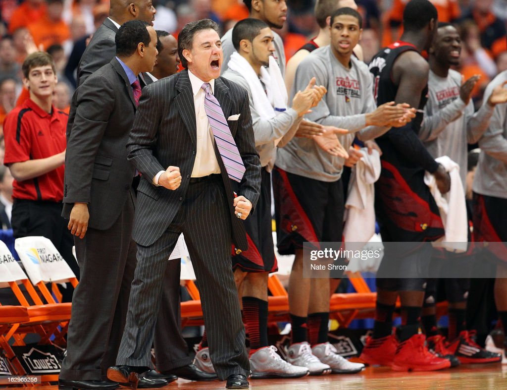 Head coach <a gi-track='captionPersonalityLinkClicked' href=/galleries/search?phrase=Rick+Pitino&family=editorial&specificpeople=210871 ng-click='$event.stopPropagation()'>Rick Pitino</a> of the Louisville Cardinals cheers from the sideline with palyers on the bench during the win against the Syracuse Orange at the Carrier Dome on March 2, 2013 in Syracuse, New York.