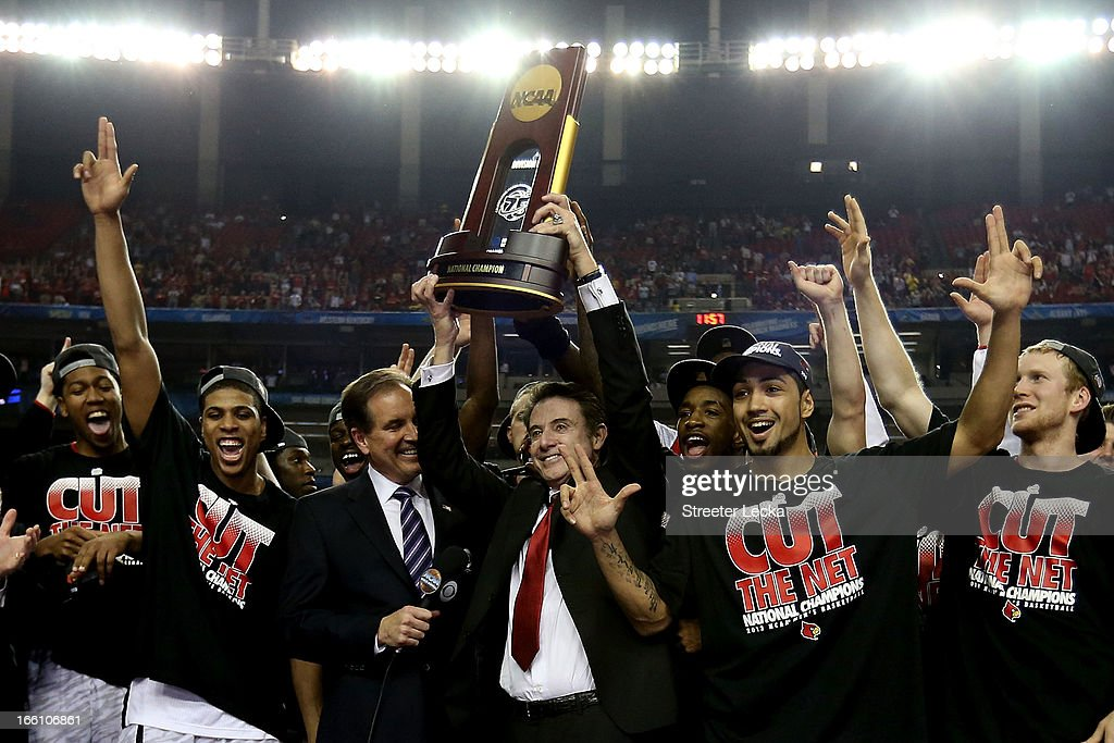 Head coach Rick Pitino of the Louisville Cardinals holds up the National Championship trophy as he celebrates with his players including Peyton Siva #3 (R of Pitino after they won 82-76 against the Michigan Wolverines during the 2013 NCAA Men's Final Four Championship at the Georgia Dome on April 8, 2013 in Atlanta, Georgia.