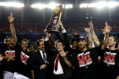 Head coach Rick Pitino of the Louisville Cardinals holds up the National Championship trophy as he celebrates with his players including Peyton Siva...