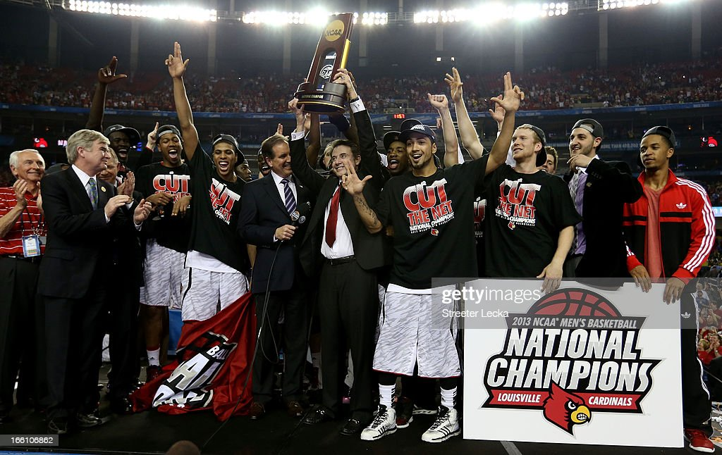 Head coach Rick Pitino of the Louisville Cardinals holds up the National Championship trophy as he celebrates with his players including Peyton Siva #3