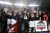 Head coach Rick Pitino of the Louisville Cardinals holds up the National Championship trophy as he celebrates with his players including Peyton Siva