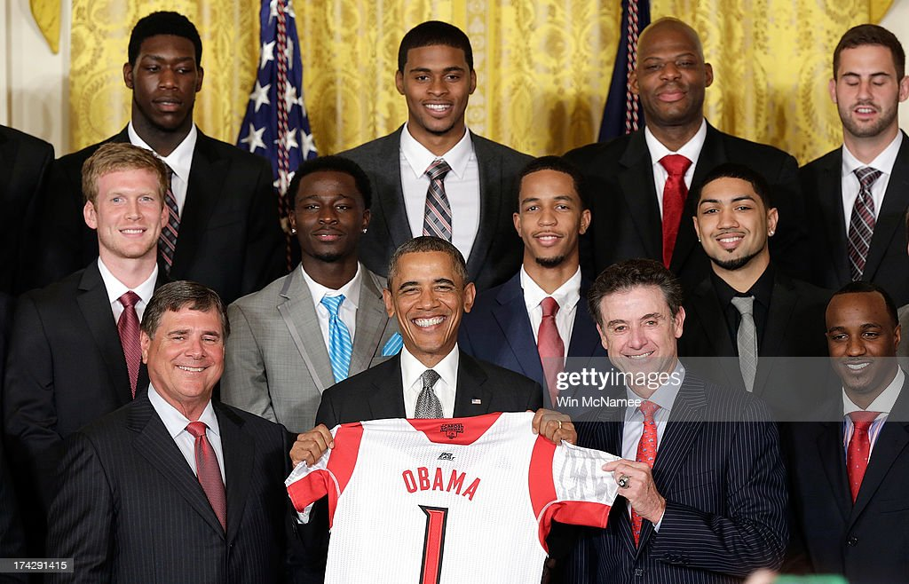 Head coach <a gi-track='captionPersonalityLinkClicked' href=/galleries/search?phrase=Rick+Pitino&family=editorial&specificpeople=210871 ng-click='$event.stopPropagation()'>Rick Pitino</a> (2nd R front row) presents U.S. President <a gi-track='captionPersonalityLinkClicked' href=/galleries/search?phrase=Barack+Obama&family=editorial&specificpeople=203260 ng-click='$event.stopPropagation()'>Barack Obama</a> with a basketball jersey from the Louisville Cardinals, the 2013 NCAA Men's Basketball Champions, during an event in the East Room of the White House July 23, 2013 in Washington, DC. The Louisville Cardinals defeated the Michigan Wolverines in the championship game by a score of 82-76.