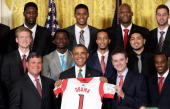 Head coach Rick Pitino presents US President Barack Obama with a basketball jersey from the Louisville Cardinals the 2013 NCAA Men's Basketball...