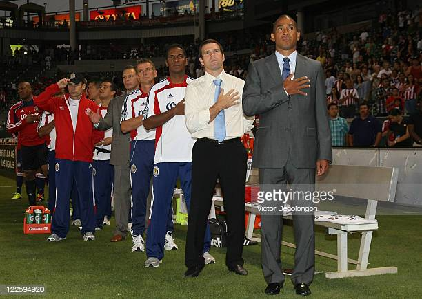 Head Coach Robin Fraser of Chivas USA and his coaching staff stand for the singing of the National Anthem prior to the start of their MLS match...
