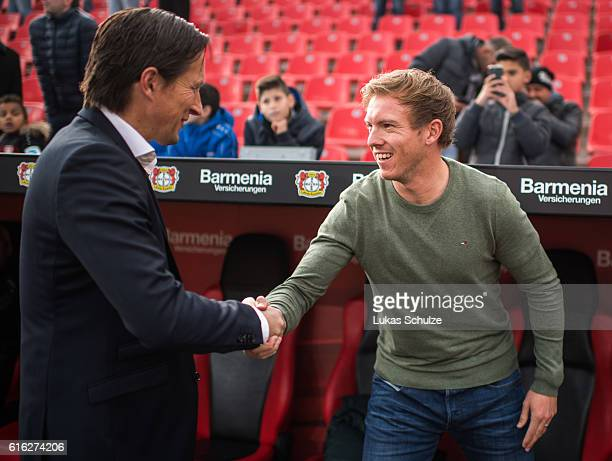 Head Coach Roger Schmidt of Leverkusen and Head Coach Julian Nagelsmann of Hoffenheim shake hands prior to the Bundesliga match between Bayer 04...