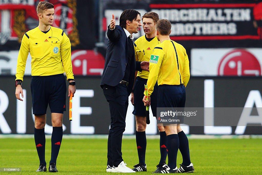 Head coach Roger Schmidt of Leverkusen discusses with referee Christian Dingert after the Bundesliga match between Bayer 04 Leverkusen and Hamburger...