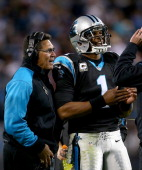 Head coach Ron Rivera and Cam Newton of the Carolina Panthers talk during a timeout during their game against the New England Patriots at Bank of...