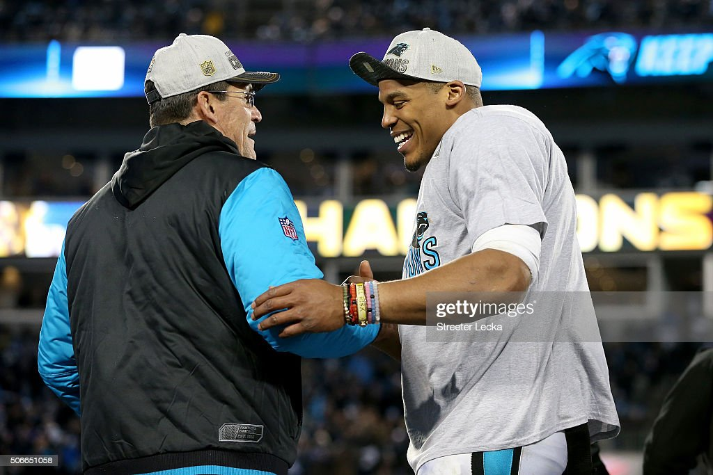Head coach Ron Rivera of the Carolina Panthers celebrates with Cam Newton after defeating the Arizona Cardinals with a score of 49 to 15 to win the...